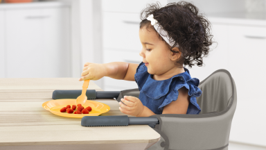 A child eats a snack at the table while seated in a Chicco clip-on high chair.