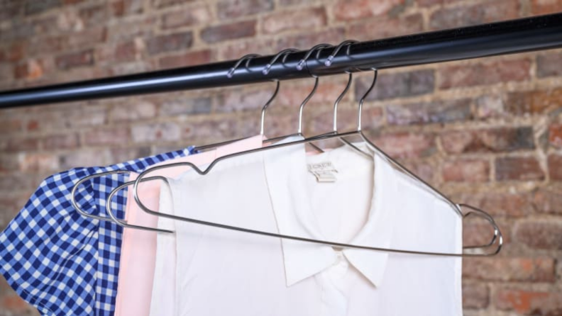 Clothes hanging from wire hangers against a brick background.