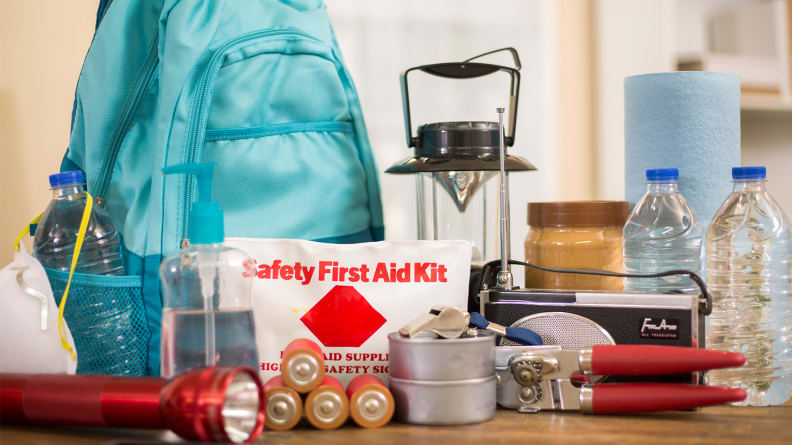 Hiking essentials like food, first-aid supplies, and a lantern laid out on a table.