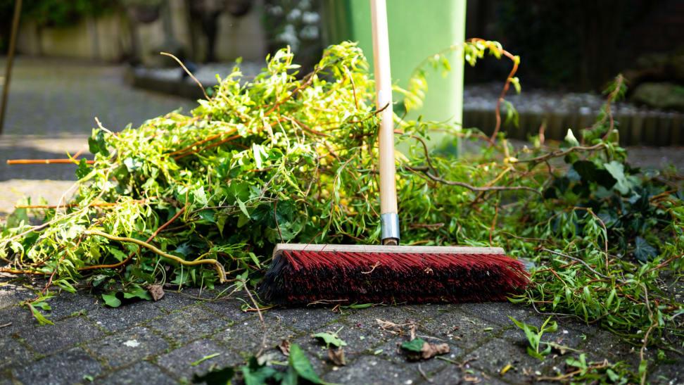 Large broom picking up branch and twig debris next to a green garbage can