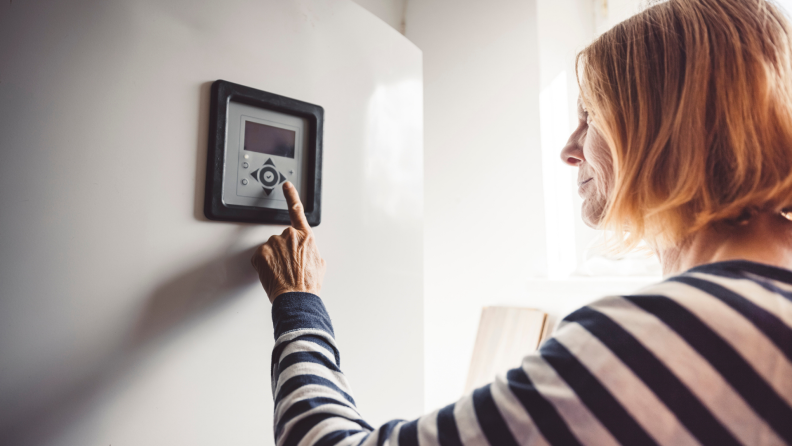 A person sets their thermostat.
