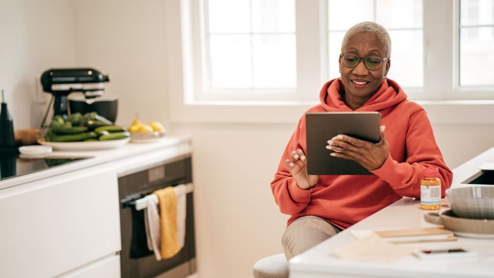 Senior woman smiling at tablet in well lit kitchen.
