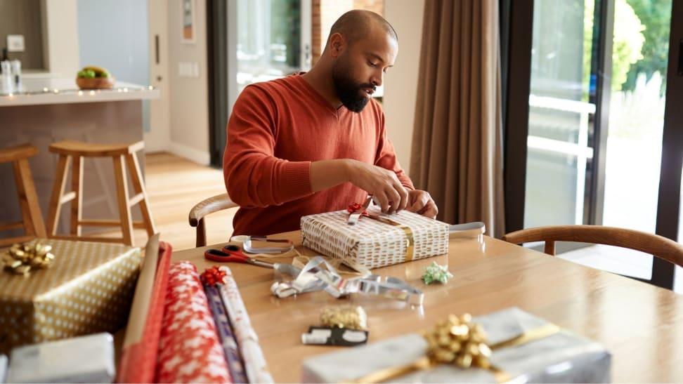 Man wrapping gifts during holiday season