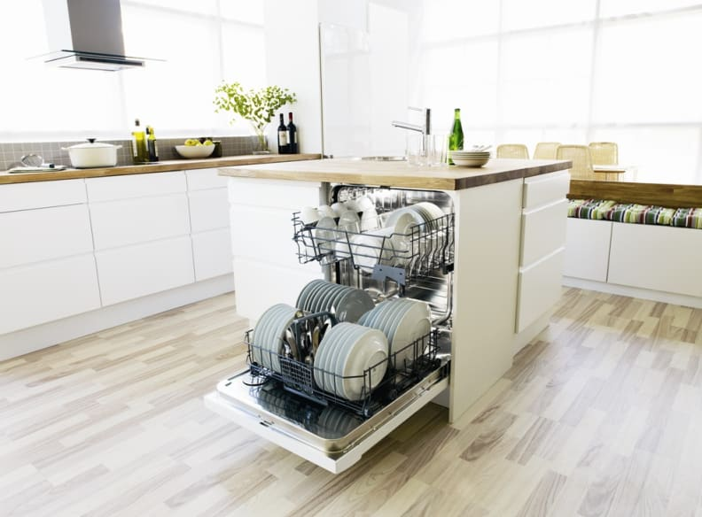 A fully integrated Asko dishwasher in the island of a transitional kitchen design.