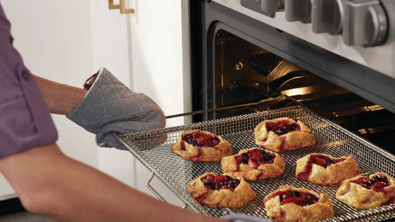 A mitten-wearing person is taking a tray of galettes with berry jam filling out of the oven.