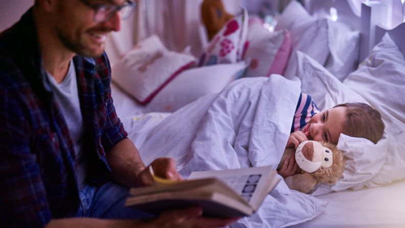 A father reads a bedtime story to his daughter.