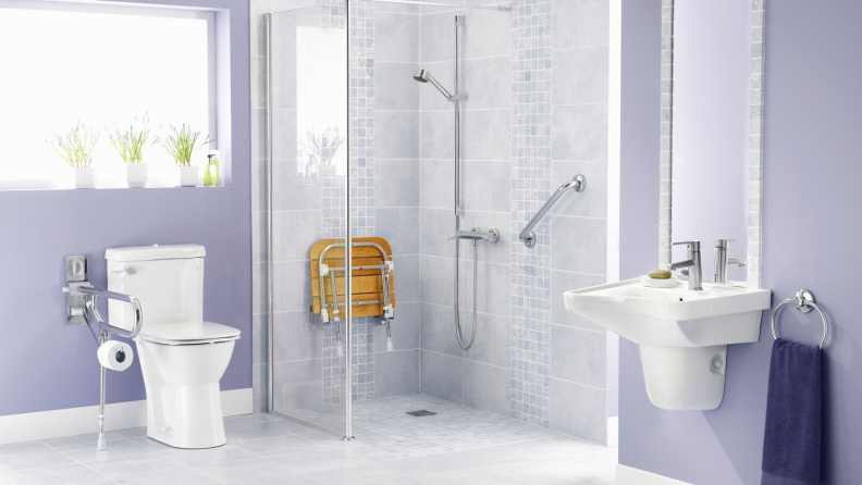 Modern bathroom with accessibly hand rails and seat in shower.