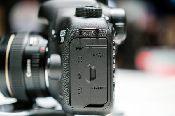 The 7D Mark II has connections for headphones, mics, USB, HDMI, flash sync, and remote control.