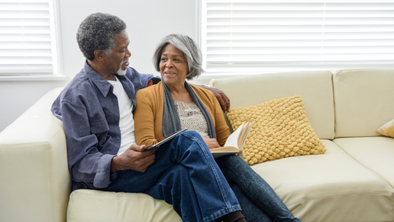 Older couple sitting on couch together, one holding a tablet and the other reading a book, facing each other smiling