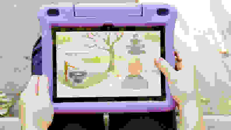 Close up of a person using a purple Amazon Fire HD 8 Kids Edition tablet.