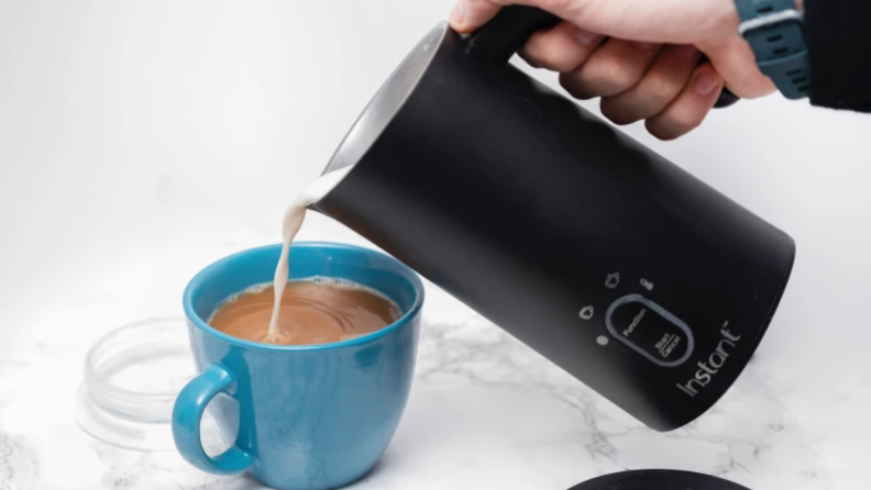 An image of a blue mug with coffee in it with foam pouring into it from a Instant