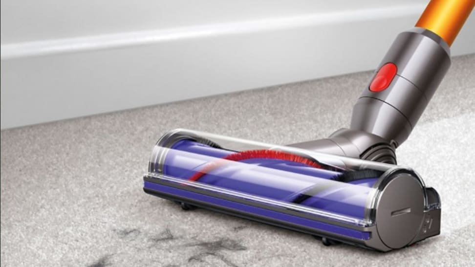 A Dyson vacuum cleans a dirty carpet.