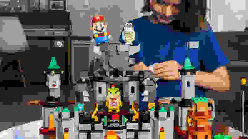 A setup of the Bowser's Castle Boss Battle expansion set, with a child building in the background.