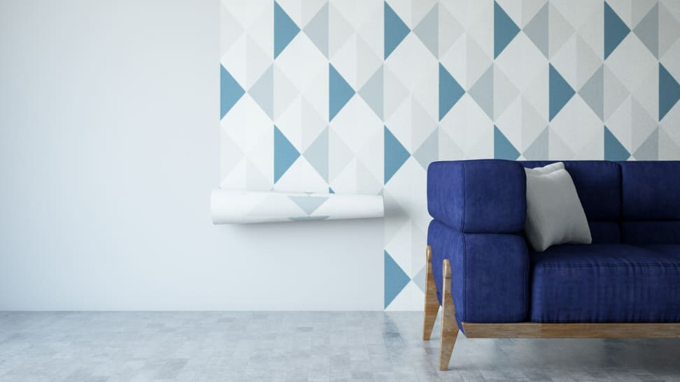 Geometric wallpaper pasted on wall with a blue couch in front of the wall.