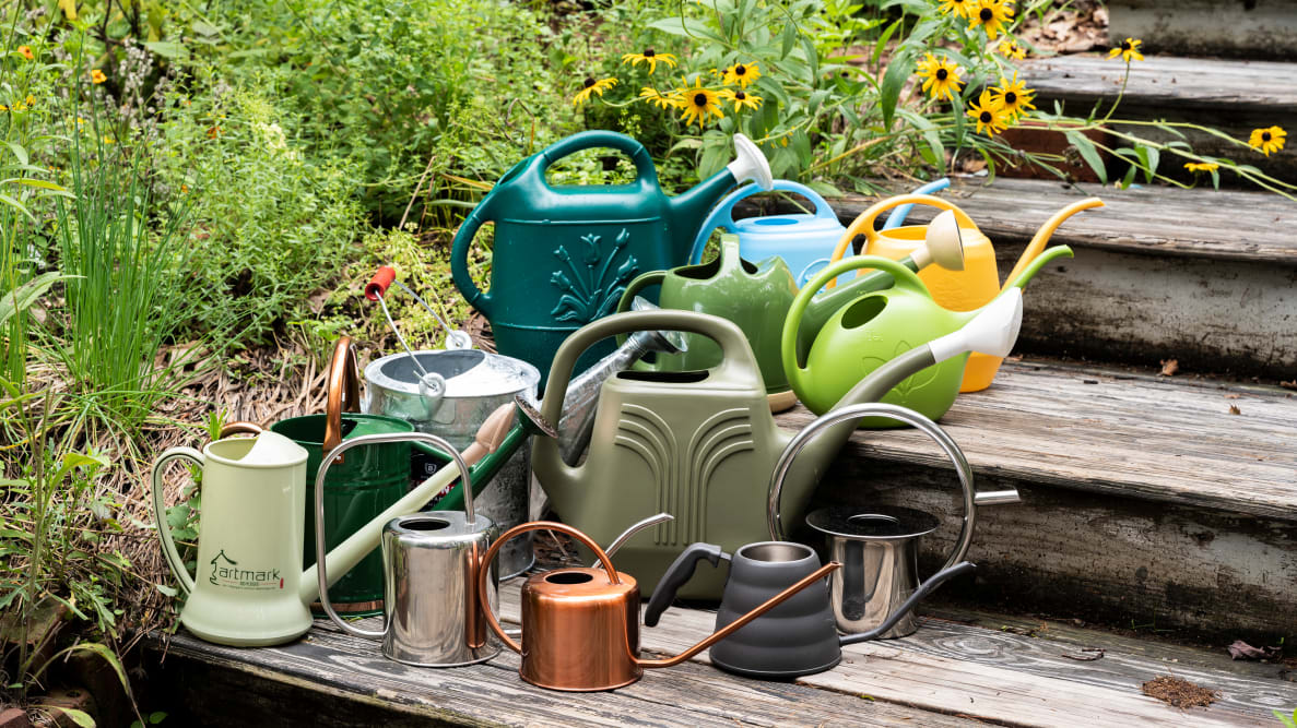 13 watering cans of different colors and sizes sit clustered on wooden steps in a garden