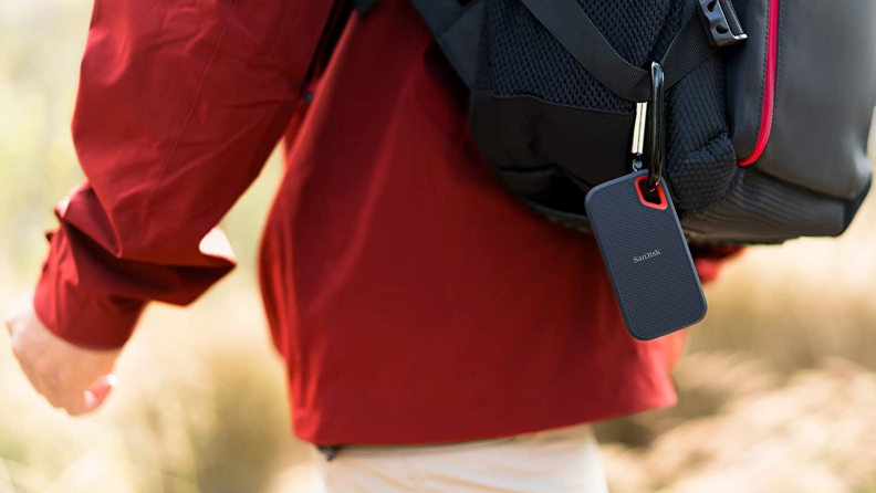 A person hikes with a SanDisk external hard drive clipped to their backpack.