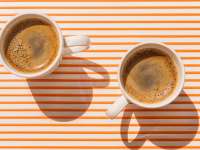Two white espresso cups filled with espresso on an orange and white striped background.