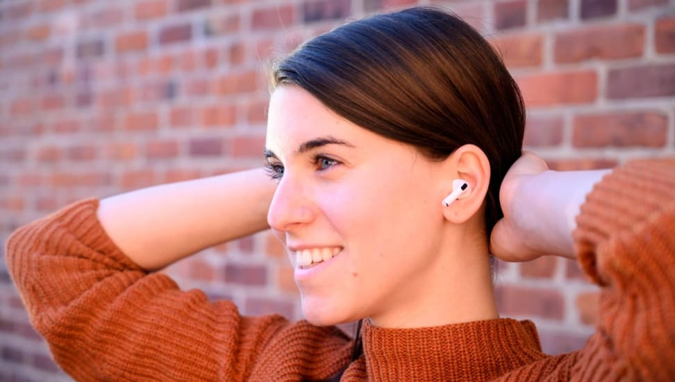A person leans against a brick wall wearing Apple Airpods.