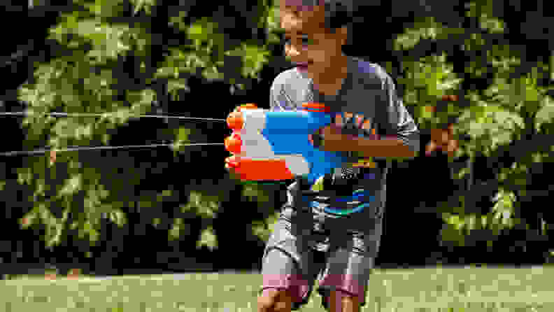 A boy shoots water from a Nerf Twin Shot Super Soaker
