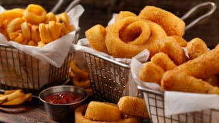 Fried onion rings and french fries are piled up in fry baskets.