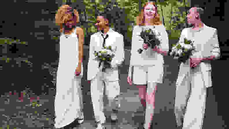 LGBT Wedding Celebration, four humans each dressed in white, one in a long dress, another in a skirt, and two in pants suits, holding bouquets.