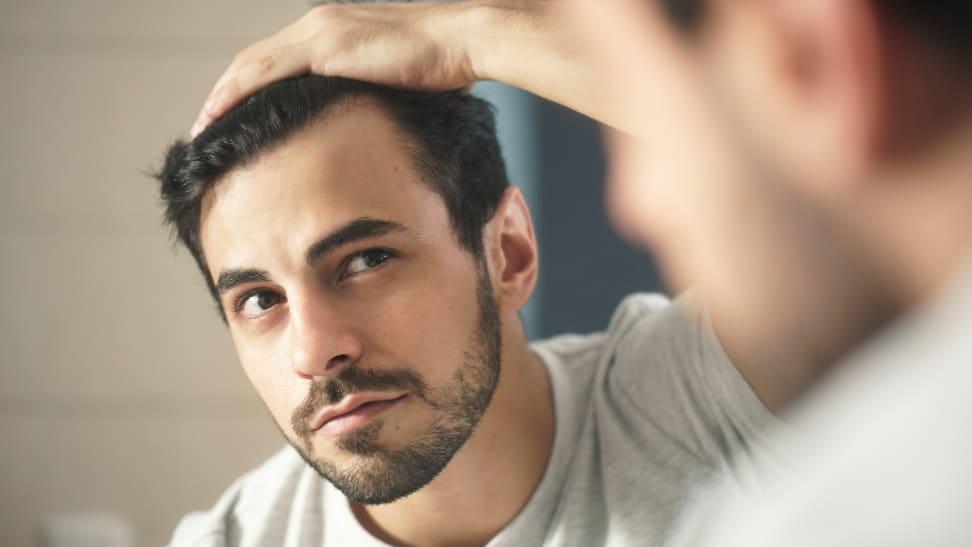 A photo of a man touching his hair.