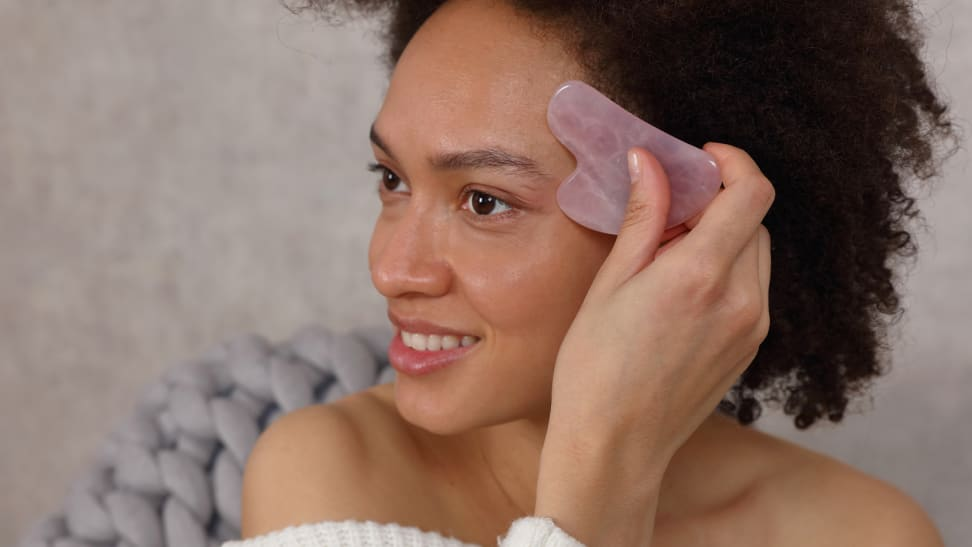 A woman using a gua sha stone to smooth her forehead.