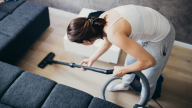 A woman cleans a hardwood floor with a vacuum