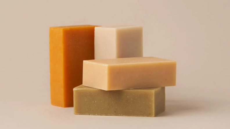 Three neutral colored By Humankind shampoo bars stacks on top of each other with an orange one standing to the left of the stack.