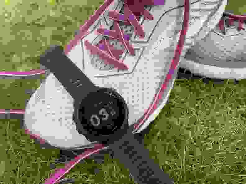 Garmin Forerunner 55 watch draped over the toe of a Brooks running shoe