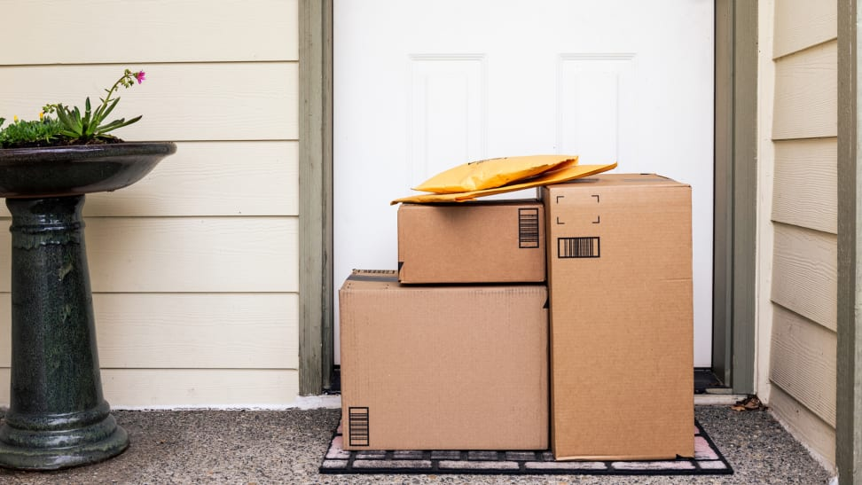 A pile of delivery boxes at the front door of a house.