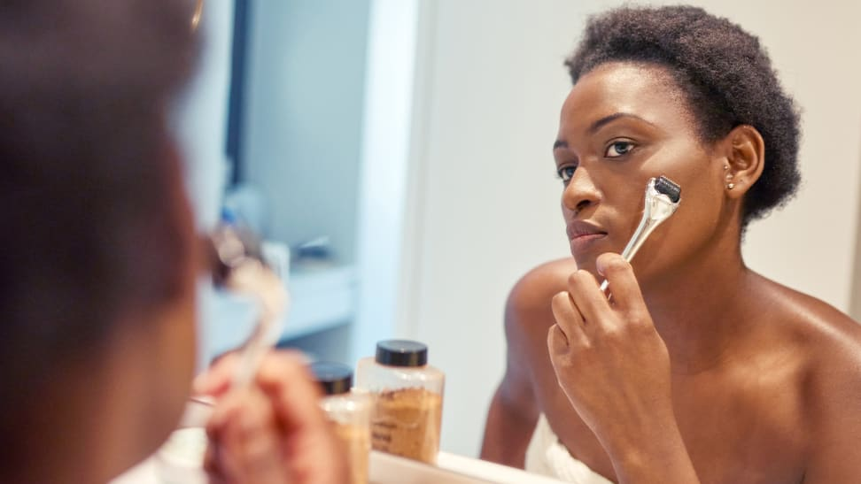 A woman looks into the mirror and holds a dermaroller up to her cheek.