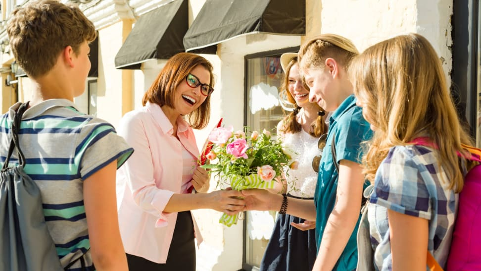 Students giving a teacher flowers.