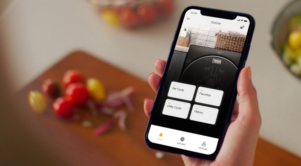 A hand holds a smart phone above a cooking board with some chopped vegetables on it. The phone's screen shows the Whirlpool app, and the user is checking on the status of their Whirlpool washing machine.