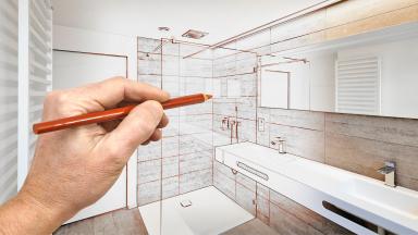 An architect draws plans for a bathroom renovation