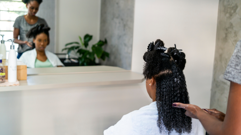 A woman with curly hair gets her hair styled in the salon