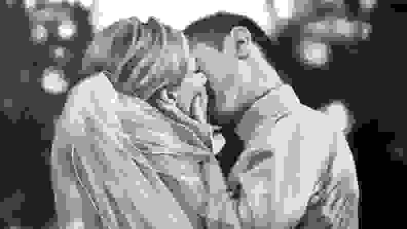 black and white portrait of married couple kissing
