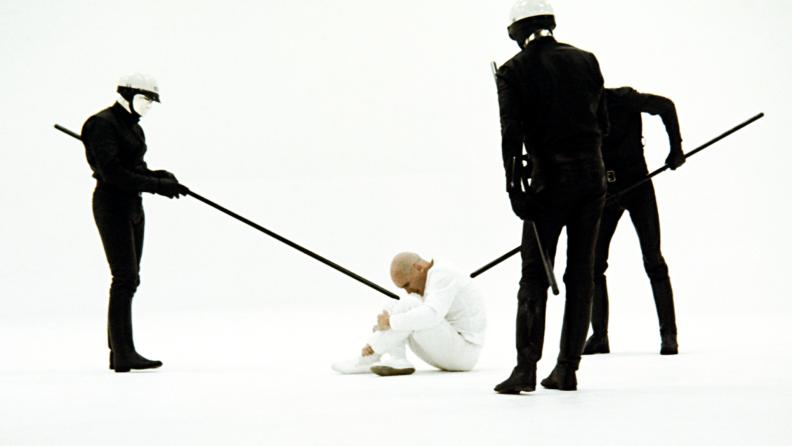 Android cops surround Robert Duvall, brandishing quarterstaffs, in the 1971 film THX 1138.
