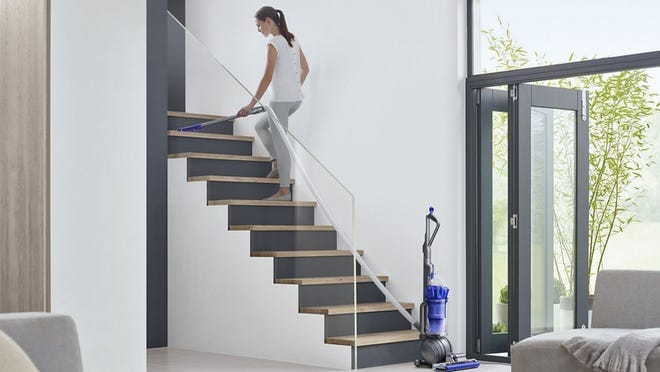 A person walks up stairs inside a home. A Dyson vacuum cleaner sits upright on the floor.
