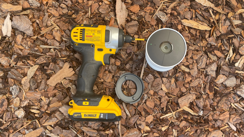 A drill, mounting base with screws, and the new Nest Cam sit on a pile of mulch.