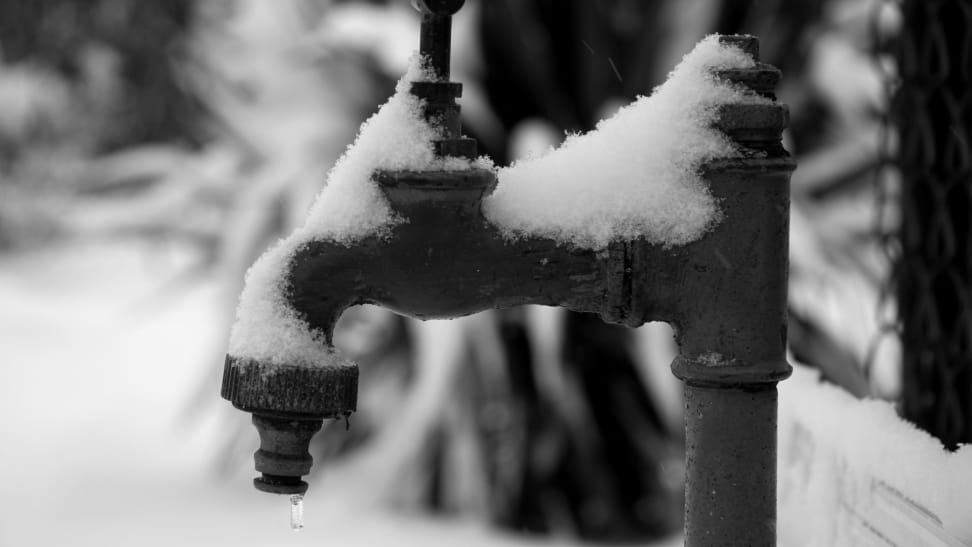 Frozen outdoor faucet with snow on top and icey water dripping out