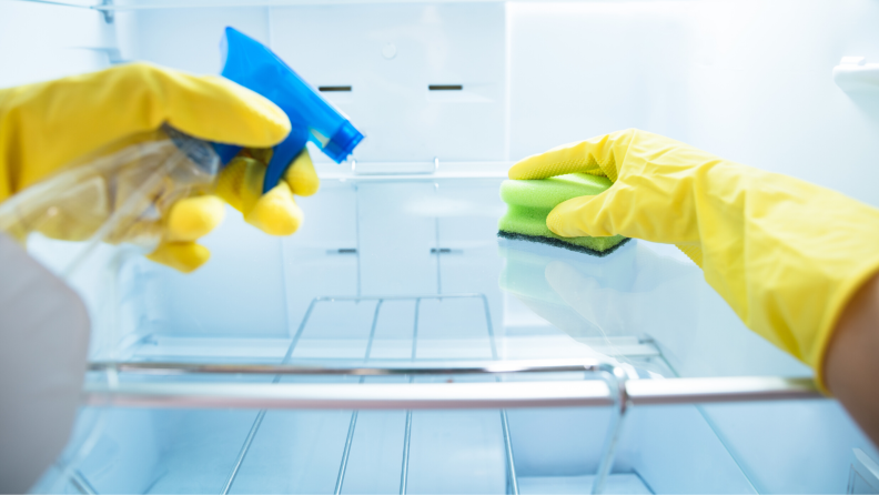 A point-of-view shot where the subject is wearing yellow rubber gloves and cleaning the inside of a fridge with a sponge.