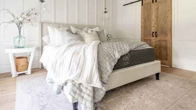 Black Puffy mattress in earth-toned bedroom with white comforter