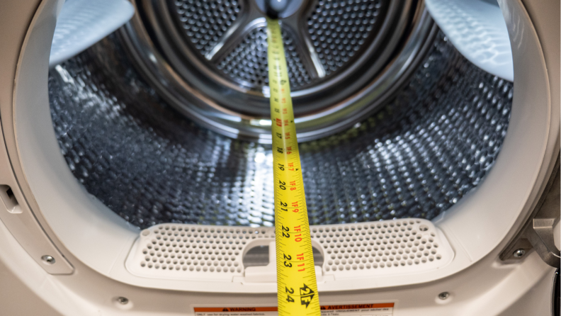 Measuring tape being used to measure the inside of a dryer from Bosch.