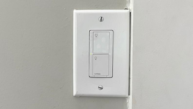 The Lutron Caséta Smart Light Switch hangs on a wall.