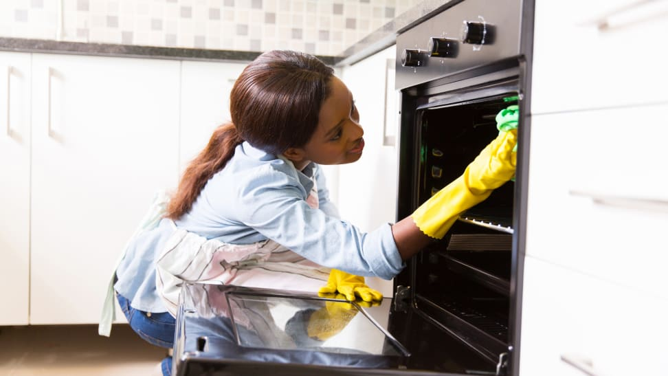 A woman cleaning her oven