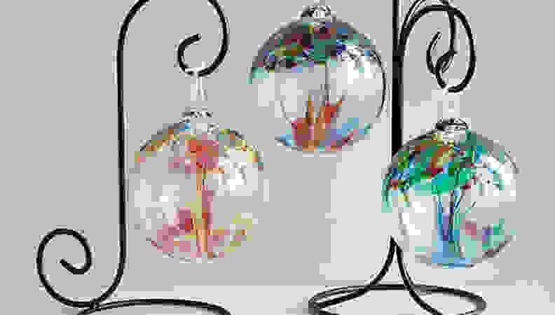 assorted colored glass globes hanging from ironlike stand on grey background.