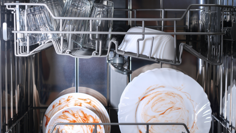 White plates in dishwasher with red sauce stains on them.