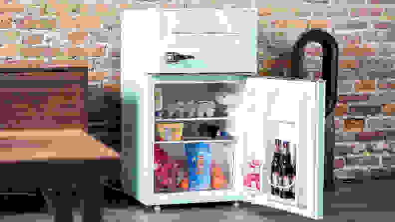 Magic Chef Retro mini fridge filled with soda, eggs, yogurt, and more food items.
