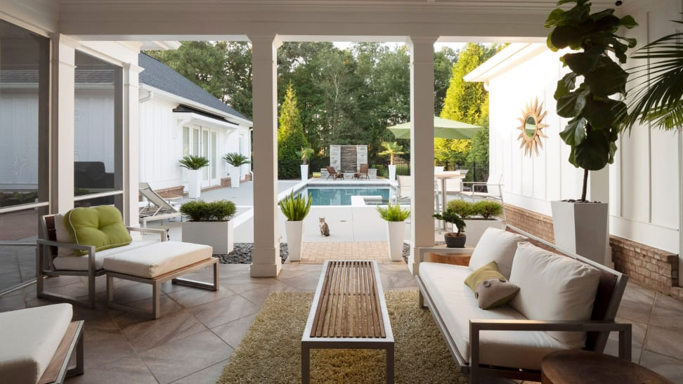 Upscale modern patio furniture with a coffee table, plants, throw pillows, and a blanket next to a pool